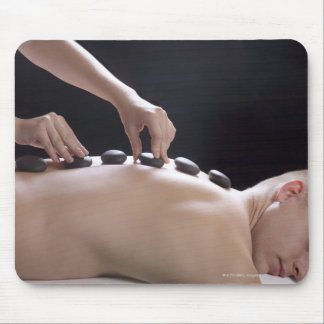 young man getting hot stone massage treatment mouse pad