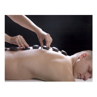young man getting hot stone massage treatment postcard