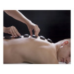 young man getting hot stone massage treatment poster