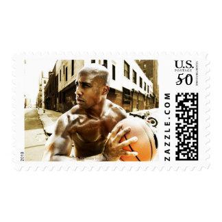 Young man holding basketball postage