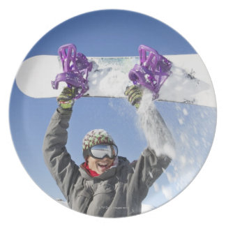 Young man holding his snowboard above his head plate
