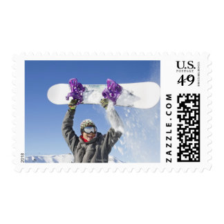 Young man holding his snowboard above his head postage stamp