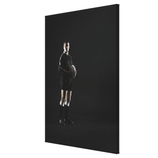 Young man holding rugby ball, portrait canvas print