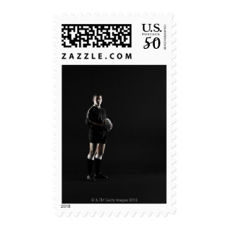 Young man holding rugby ball, portrait postage