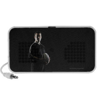 Young man holding rugby ball, portrait mp3 speaker