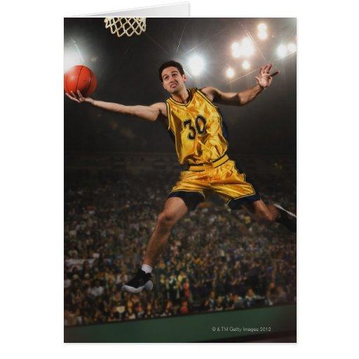 Young man jumping and holding basketball greeting card