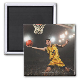 Young man jumping and holding basketball magnet