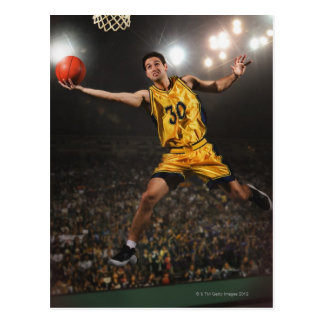 Young man jumping and holding basketball postcard