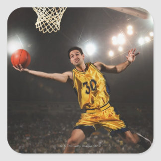 Young man jumping and holding basketball square sticker