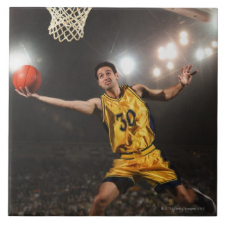 Young man jumping and holding basketball tile