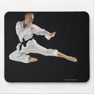 Young man performing karate kick on black mouse pad