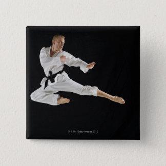Young man performing karate kick on black pinback button