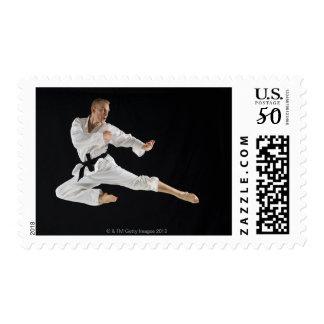 Young man performing karate kick on black postage