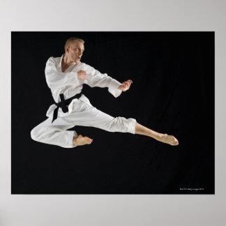 Young man performing karate kick on black poster