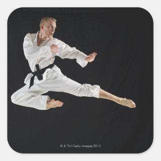 Young man performing karate kick on black square sticker