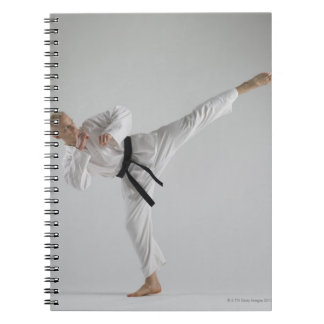 Young man performing karate kick on white notebook