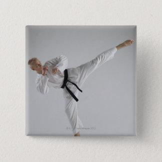 Young man performing karate kick on white pinback button