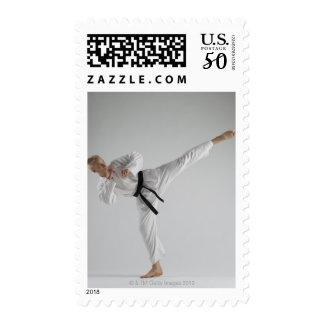 Young man performing karate kick on white postage
