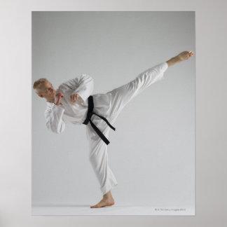 Young man performing karate kick on white poster
