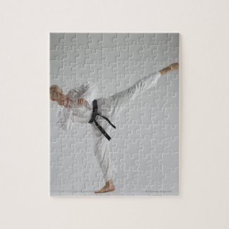 Young man performing karate kick on white puzzle