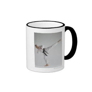 Young man performing karate kick on white ringer mug