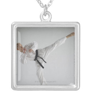 Young man performing karate kick on white silver plated necklace
