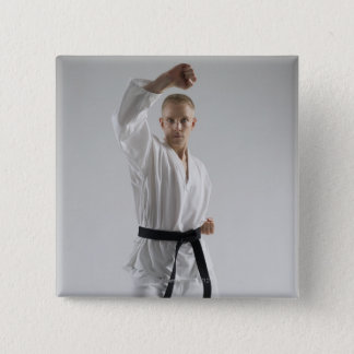 Young man performing karate stance on white button