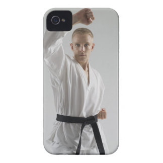 Young man performing karate stance on white iPhone 4 cover