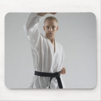 Young man performing karate stance on white mouse pad