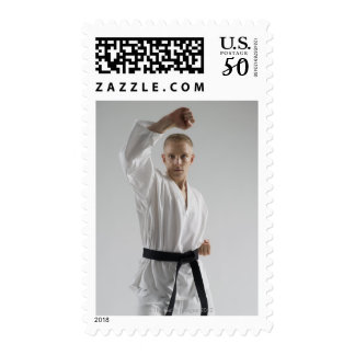 Young man performing karate stance on white postage