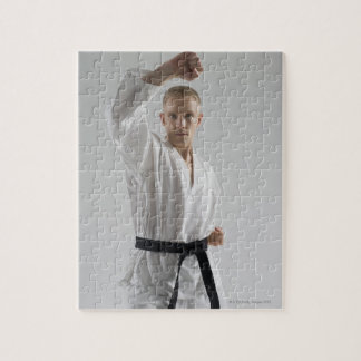 Young man performing karate stance on white puzzle