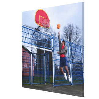 Young man playing basketball outdoors canvas print