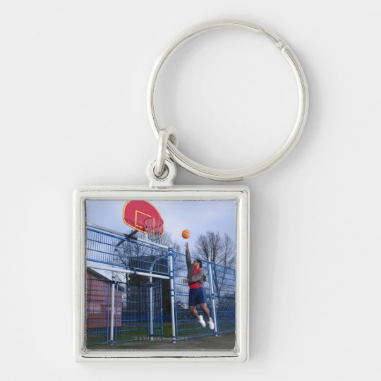 Young man playing basketball outdoors keychain