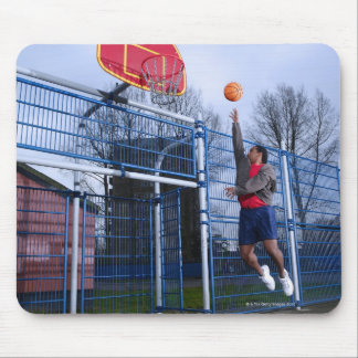 Young man playing basketball outdoors mouse pad