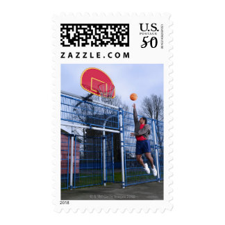 Young man playing basketball outdoors postage