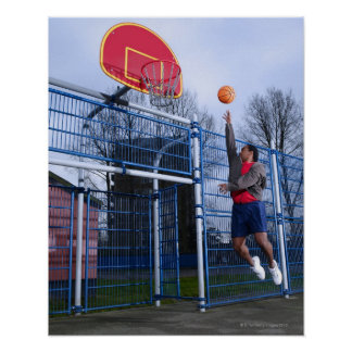 Young man playing basketball outdoors poster