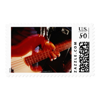 Young man playing bass guitar, close-up of hand postage