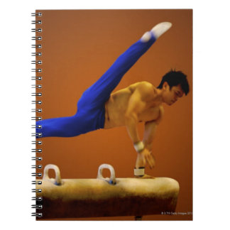 Young man practicing gymnastics on the pommel note book