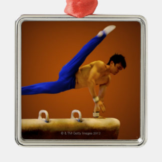 Young man practicing gymnastics on the pommel christmas ornaments
