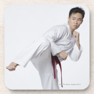 Young man practicing side kick beverage coaster