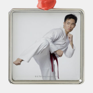 Young man practicing side kick metal ornament