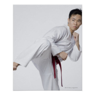 Young man practicing side kick poster