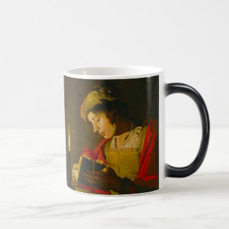Young man reading by candlelight coffee mugs