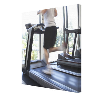 Young man running on a treadmill at health club, canvas print