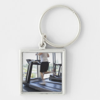Young man running on a treadmill at health club, Silver-Colored square keychain