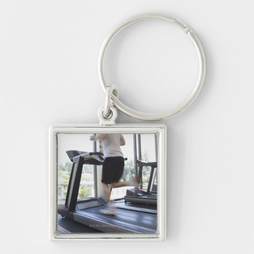 Young man running on a treadmill at health club, key chains