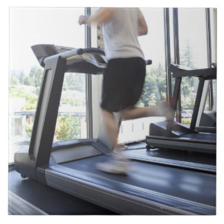 Young man running on a treadmill at health club, large square tile