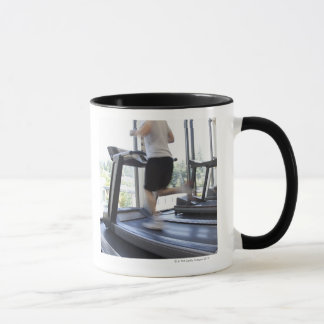 Young man running on a treadmill at health club, mug