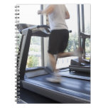 Young man running on a treadmill at health club, note books