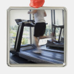 Young man running on a treadmill at health club, ornament